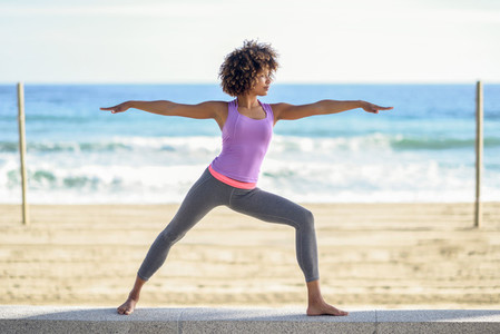 Black woman afro hairstyle doing yoga in warrior asana in the