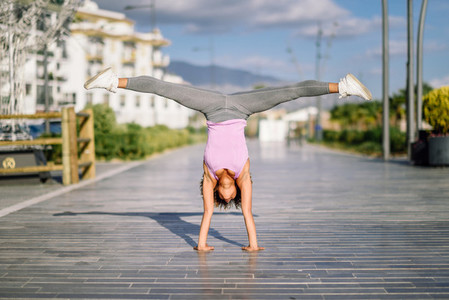 Black fit woman doing fitness acrobatics in urban background