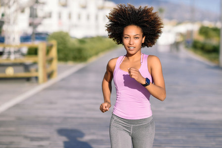 Black woman afro hairstyle running outdoors in urban road