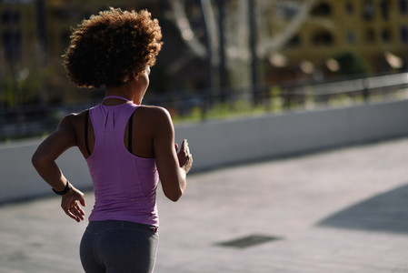 Black woman afro hairstyle running outdoors at Sunset
