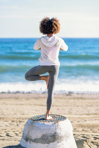 Rear view of young black woman doing yoga in the beach