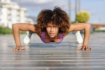 Black fit woman doing pushups on urban floor