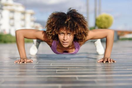 Black fit woman doing pushups on urban floor