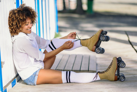 Young black woman sitting on wooden floor puts on skates