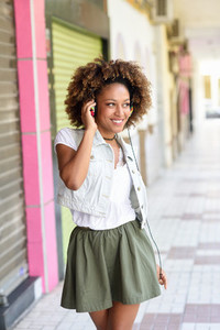 Young black woman afro hairstyle in urban street with headphon
