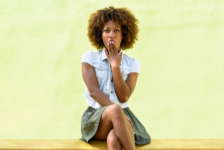 Black woman afro hairstyle sitting with a surprise face