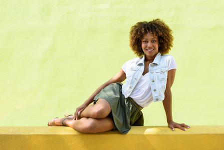 Young black woman afro hairstyle sitting on an urban wall