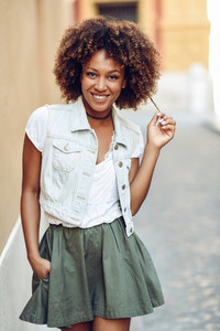 Young black girl afro hairstyle smiling in urban background
