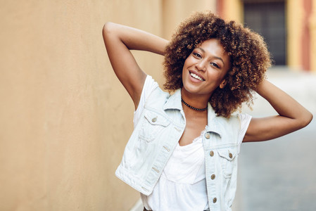 Young black woman afro hairstyle smiling in urban background