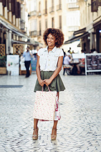 Black woman  afro hairstyle  with shopping bags in the street
