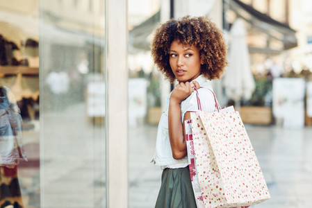 Young black woman afro hairstyle looking at a shop window