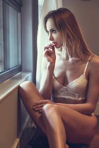 Beautiful blonde woman in white lingerie posing near a window