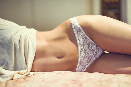 Unrecognizable woman with beautiful body in white lingerie