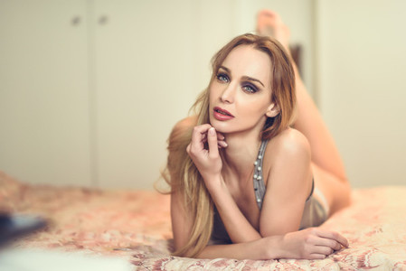 Beautiful blonde woman lying on the bed