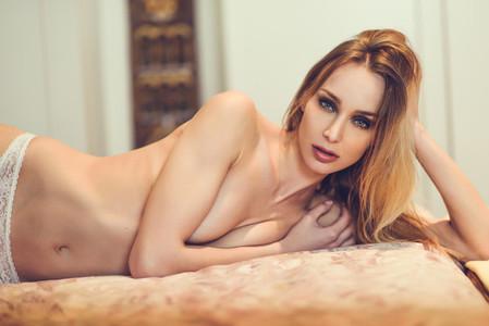 Topless blonde woman in white panties posing on her bed