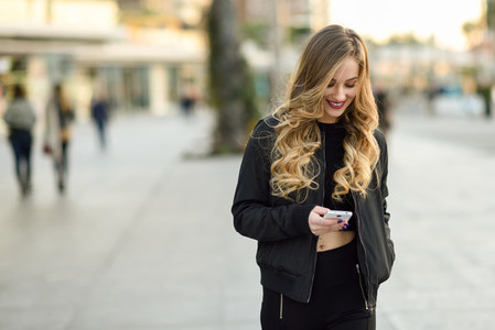 Blonde woman texting with her smartphone in urban background