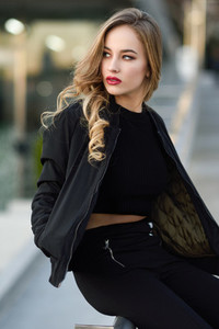 Beautiful young girl wearing black jacket sitting in the street