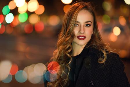 Woman wearing black jacket in the street with defocused lights