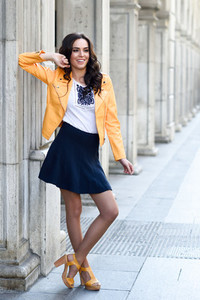 Young brunette woman smiling in urban background