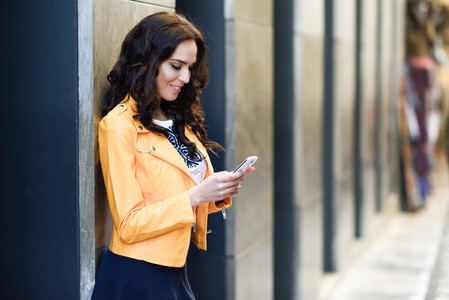 Young brunette woman with smart phone in urban background