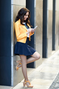 Young brunette woman with smartphone in urban background