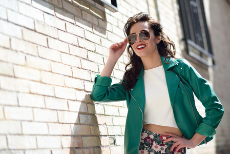 Young brunette woman with sunglasses in urban background