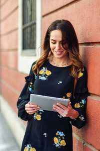 Smiling young woman using digital tablet outdoors