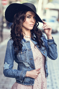 Young brunette woman standing in urban background