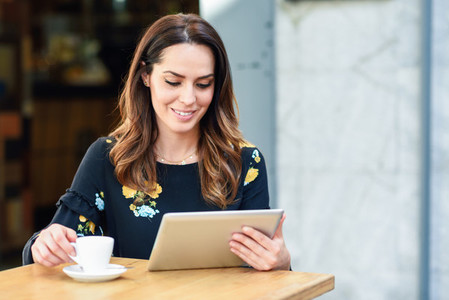 Middle aged woman using tablet on coffee break in urban cafe bar