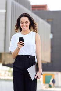 Businesswoman working with her smart phone and laptop outdoors
