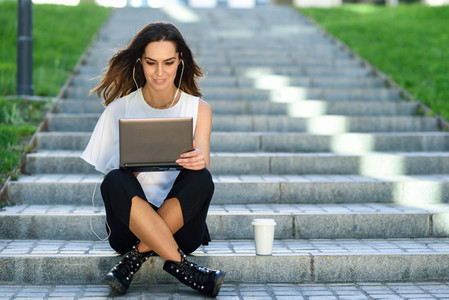 Middle age businesswoman working with her laptop computer sitting on the floor