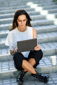 Young woman working with her laptop computer sitting on the floor