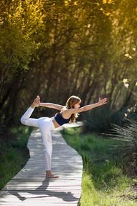 Young beautiful woman doing yoga in nature