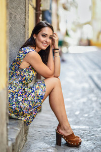 Happy young woman with blue eyes smiling sitting on urban step