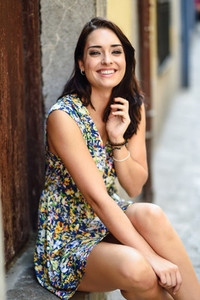 Girl with blue eyes smiling sitting on urban step