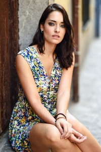 Beautiful young woman with blue eyes sitting on urban step