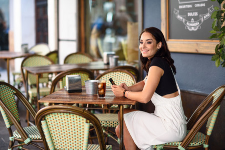 Smiling woman with blue eyes sitting on urban cafe using smart phone