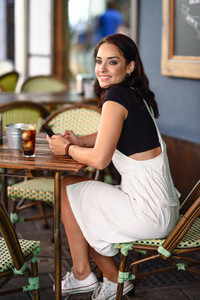 Girl with blue eyes sitting on urban cafe using smart phone smil