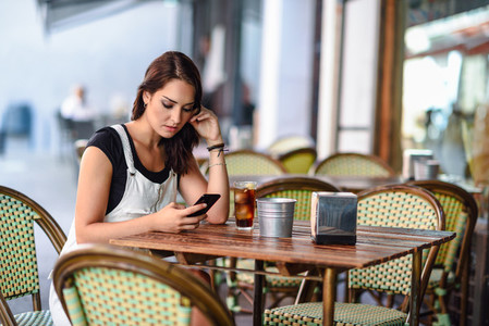 Girl with blue eyes sitting on urban cafe using smart phone