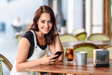 Woman with blue eyes sitting on urban cafe using smart phone