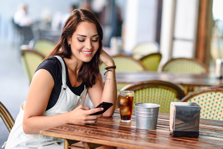Smiling woman with blue eyes sitting on urban cafe using smart p