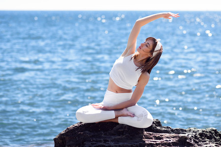 Young woman doing yoga in the beach wearing white clothes