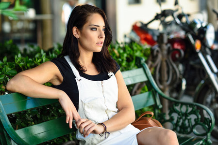 Beautiful young woman with blue eyes looking away sitting on urban bench