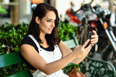 Young woman taking photographs with her smart phone outdoors