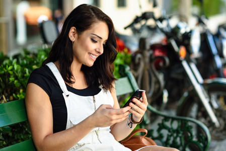 Smiling young woman using her smart phone outdoors