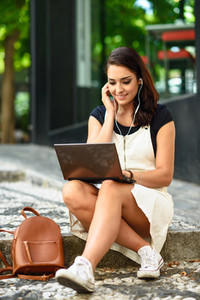 Student woman using laptop computer sitting on urban steps