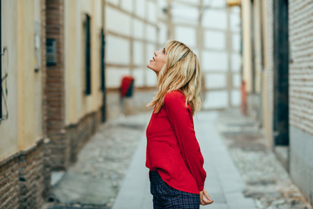 Happy young blond woman walking down the street
