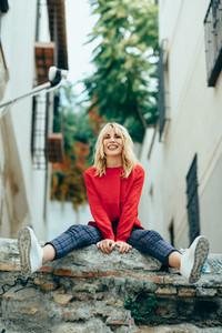Smiling blonde girl with red shirt enjoying life outdoors