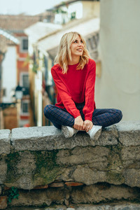 Smiling blonde girl with red shirt enjoying life outdoors