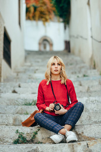 Young woman taking photographs with an old camera in a beautiful